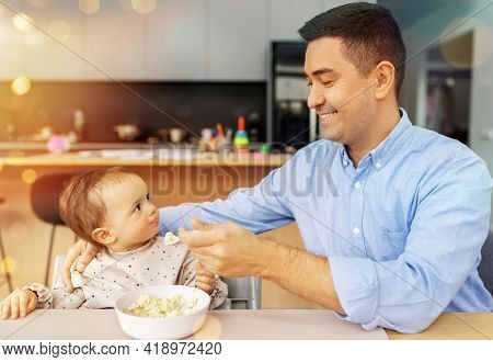 family, food, eating and people concept - happy smiling middle-aged father feeding little baby daughter sitting in highchair with puree by spoon at home