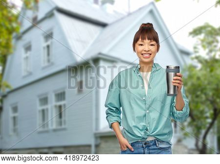 sustainability and people concept - portrait of young asian woman in turquoise shirt with thermo cup or tumbler for hot drinks over living house background