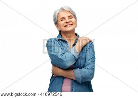 self-care, retirement and old people concept - portrait of smiling senior woman in denim shirt over white background