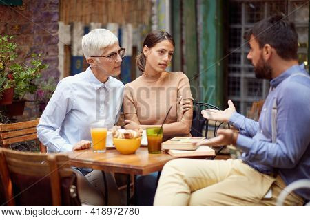 The young man defends himself from a verbal attack by his female friends of different generations while they having a drink in a tense atmosphere at a bar. Leisure, bar, friendship, outdoor