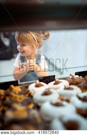 A little girl can't wait to try delicious donuts of irresistible appearance in a pastry shop. Pastry, dessert, sweet