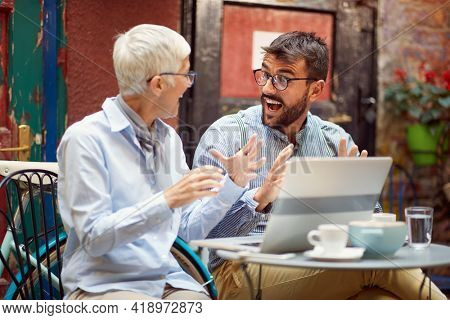 An elderly woman has an interesting talk with her young male friend while spending free time at bar's garden together on a beautiful day. Leisure, bar, friendship, outdoor
