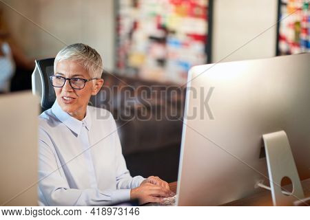 An elderly business woman sitting and working at a desk in a working atmosphere at workplace. Business, office, job