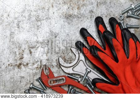 Mechanic tools wrench pliers protective gloves bolts and nuts on metal background