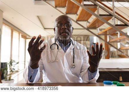 Portrait of african american senior male doctor talking looking at the camera at home. distant communication and telemedicine consultation concept.