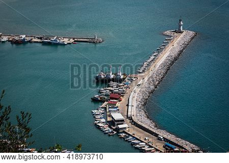 Top View Of A Pier  With A Beautiful White Lighthouse And A Pier With Many Boats And Yachts On The B
