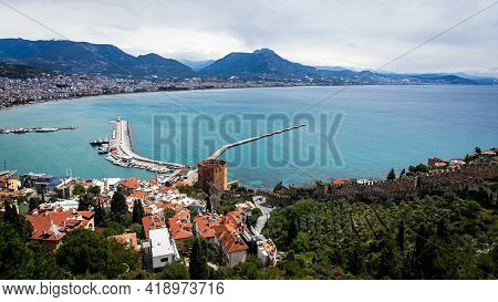 Top View Of A Pier With A Red Brick Fortress Tower With A Beautiful White Lighthouse And A Pier With