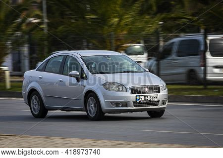 Alanya, Turkey - April 16 2021:  Silver  Fiat Albea  Is Driving Fast On The Street On A Warm Summer
