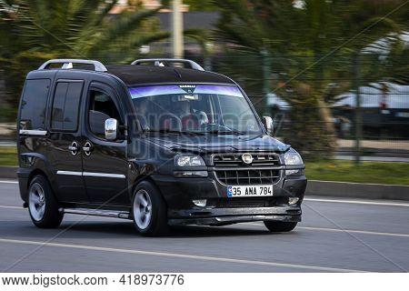 Alanya, Turkey - April 16 2021:  Black Fiat Doblo   Is Driving Fast On The Street On A Warm Summer D