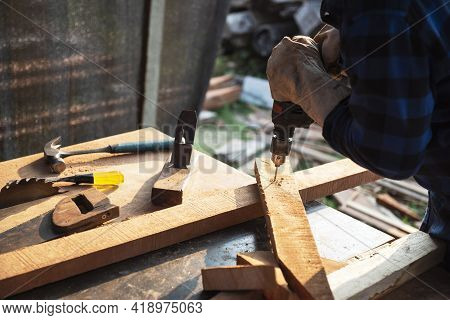 Carpenter Drills A Hole With An Electrical Drill Carpenter Doing His Job In Carpentry Workshop.