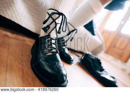 Preparing For A Scottish Wedding. Man In A Kilt, High Socks And Shoes Laced With Long Laces. Nearby