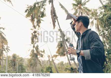 A Man With Backpack Hiking Wipe The Sweat And Hold The Water Bottle On The Road In Forest. Backpack
