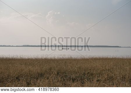 Small Boat In Middle Of Reservoir, Overlooking A Distant Island.
