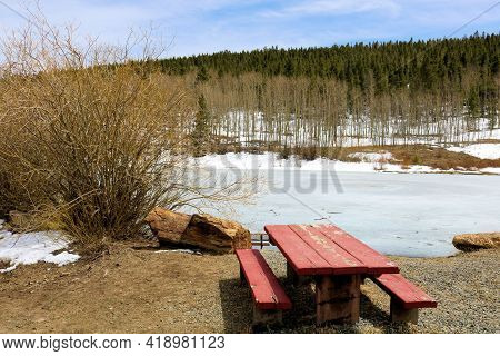 Rustic Wooden Bench For Picnics Taken At A Park With A Frozen Pond Including An Aspen And Pine Fores