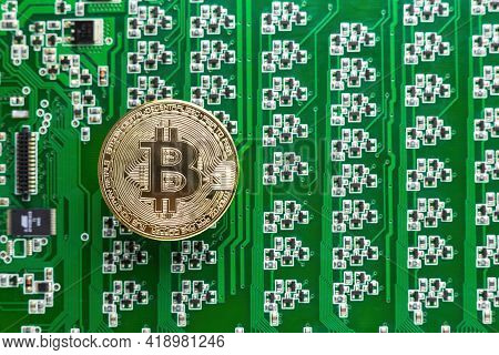 Gold Bitcoin Coin On The Background Of A Green Circuit Board With Many Transistors