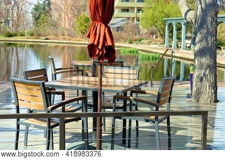 April 26, 2021 In Denver, Co:  Outdoor Patio Furniture Including A Table And Chairs On A Wooden Deck