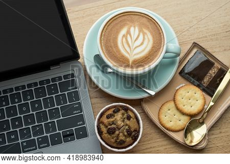 Close-up Of Hot Coffee Latte With Latte Art Milk Foam In Cup Mug And Homemade Banana Cup Cake With L
