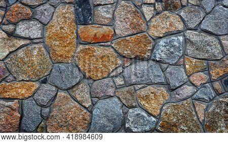 Stone Wall. Wall Of Granite Blocks. A Masonry Wall Of Multicolored Stones Or Blocks