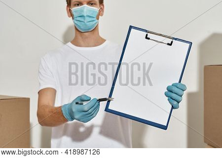 Picture Of Deliveryman Holding Clipboard And A Pen , Boxes On Both Sides, Deliveryman Asks For Fill