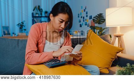 Asian Lady Feel Stress And Worried With Bill And Invoice Credit Card Calculating Loan On Sofa At Hom