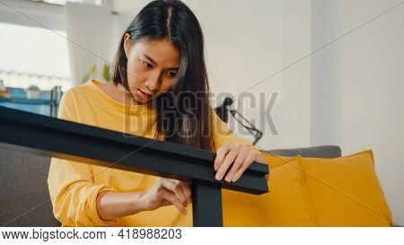 Happy Asian Young Woman Unpacking Box And Reading The Instructions To Assemble New Furniture Decorat