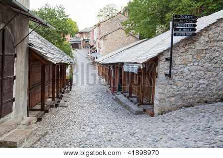 MOSTAR, BOSNIA - AUGUST 10, 2012: Pebble stone streets in old town on August 10, 2012 in Mostar, Bosnia. This old town founded in 1452, was mostly destroyed during the Bosnian war from 1991 to 1995.