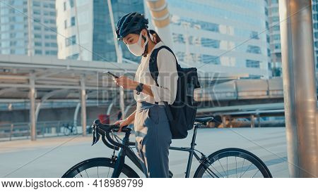 Asian Businesswoman Carry Backpack Wear Anti Virus Protection Mask Take Bicycle Walk And Check Phone