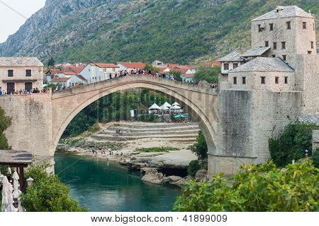 MOSTAR, BOSNIA - AUGUST 9, 2012: Tourists on Stari Most bridge on August 9, 2012 in Mostar, Bosnia. The 16th century bridge was reconstructed in 2004, after its destruction in 199 in the Bosnian war.