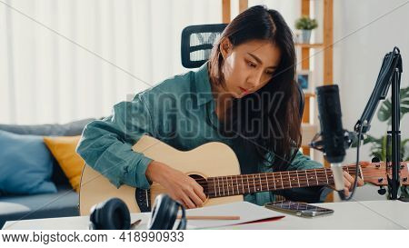 Happy Asia Woman Songwriter Play Acoustic Guitar Listen Song From Smartphone Think And Write Notes L