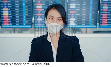 Asian Business Girl Wear Face Mask Stand In Front Of Board Flight Show Time Look At Camera Internati