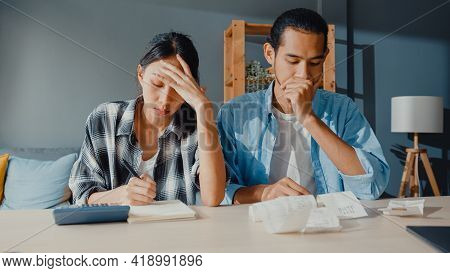 Stress Asia Couple Man And Woman Use Calculator For Calculate Family Budget, Debts, Monthly Expenses