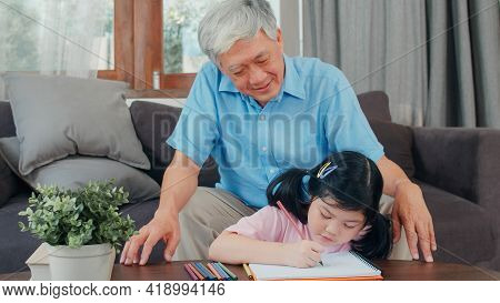 Asian Grandfather Teach Granddaughter Drawing And Doing Homework At Home. Senior Chinese, Grandpa Ha