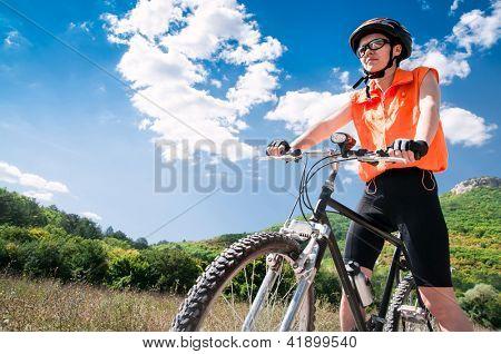 Mountain female Biker and blue sky background
