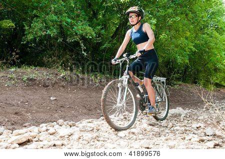 Female Cyclist rides through the forest