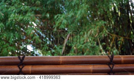 Two Dark Brown Bamboo Arrangement With Black Rope, Blurred Bamboo Leaf Background. Can Be A Design B