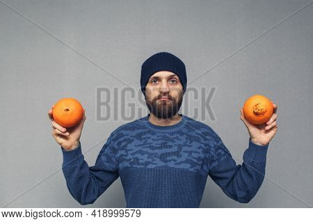Bearded Man Shows Normal And Ugly Oranges, Concept Of Hemorrhoids Or Proctological Diseases.