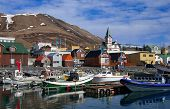 Boats for fishing and for whale watching tours gather at the port of Husavik, Iceland. poster
