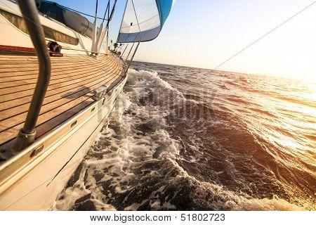 Yacht sailing towards the sunset. Luxury yachts.