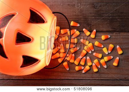 Halloween Jack-o-Lantern with candy corn spilling out onto rustic wood surface.