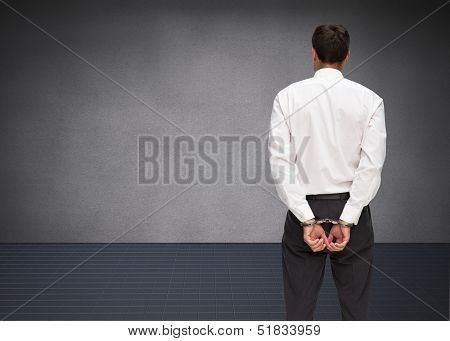Composite image of young businessman wearing handcuffs in grey room