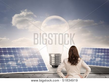Composite image of businesswoman standing back to camera with hand on hips in front of light bulb and solar panels poster