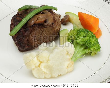 Beef tournedos (tenderloin fillet steak) served with mushrooms, steamed beans, courgettes, cauliflower, carrot and broccoli, a minimalist modern take on a traditional favourite.