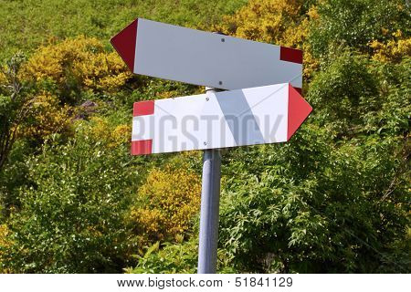 Two empty fingerposts in the forest of the Italian Alps