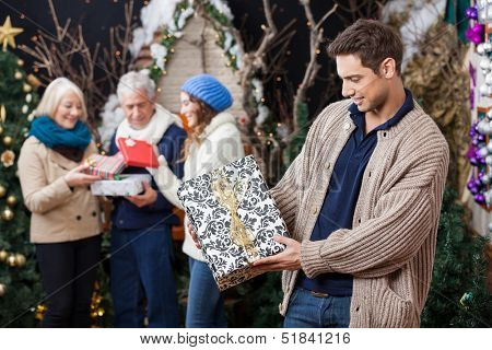 Young man looking at Christmas present with family standing in background at store