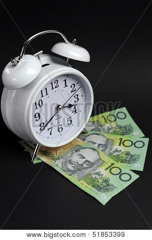 White Old Fashion Alarm Clock With Australian Hundred Dollar Notes On Black Background For Time And