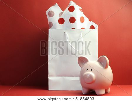 Savings Concept With White Shopping Bag, Red Polka Dot Tissue Paper, And Cute Pink Piggy Bank Agains