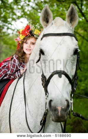 Little girl in floral wreath riding horse in the forest poster