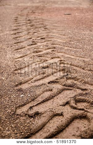 Tyre Tracks In The Sandstone Background.