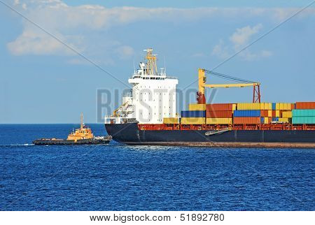 Tugboat assisting container cargo ship to harbor quayside poster