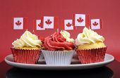 Red and White cupcakes with Canadian maple leaf national flags against a red background for Canada Day or Canadian national holidays. poster